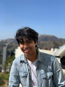 Picture of Hamza, one of the podcast hosts, smiling in front of a naturescape